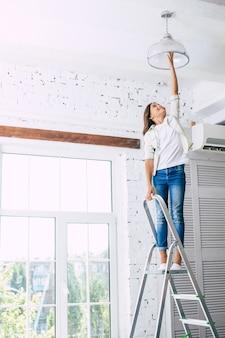 白い服を着たかわいい女の子が自分でランプの電球を交換しようとしているはしごの上に立っています