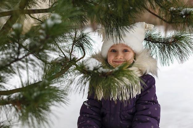 크리스마스 트리 근처 눈 속에서 겨울 옷을 입은 귀여운 소녀