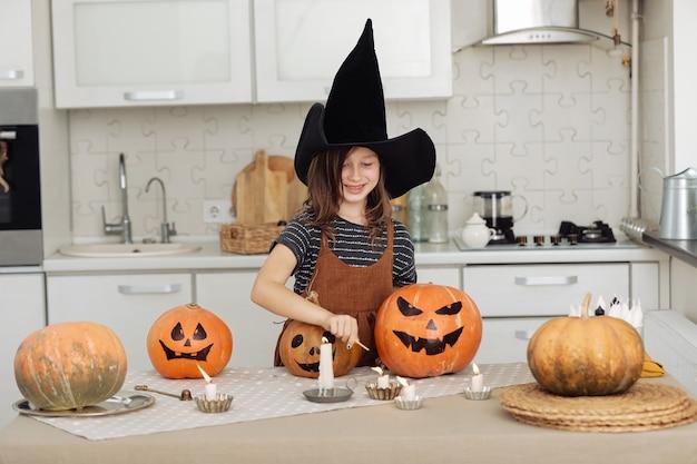 Милая маленькая девочка в костюме ведьмы с резьбой по тыкве