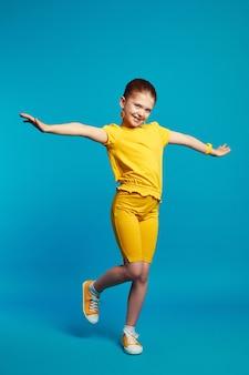 Милая маленькая девочка в желтом наряде улыбается и танцует на синем