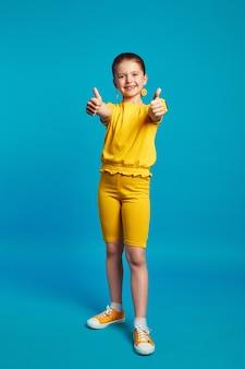Милая маленькая девочка в желтом наряде улыбается и показывает палец вверх