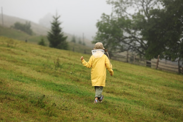 黄色いレインコートを着たかわいい女の子が霧の山を歩いています