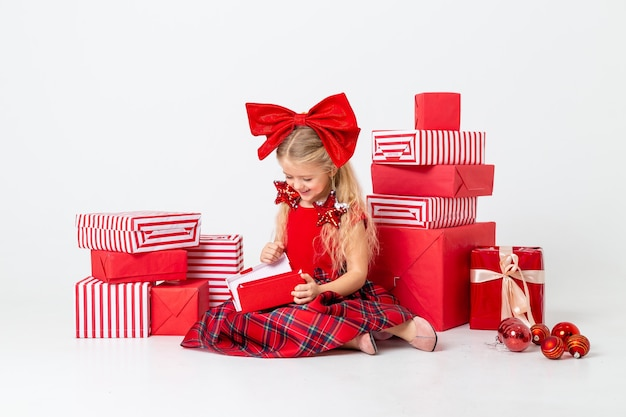 Cute little girl is being considered for christmas. white background, large gift boxes, space for text. the concept of christmas
