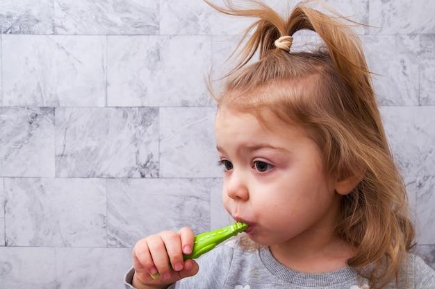 Милая маленькая девочка чистит зубы в ванной. концепция стоматологической помощи