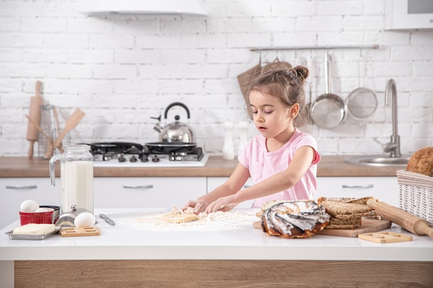 A cute little girl is cooking homemade cakes on a spacious bright kitchen.