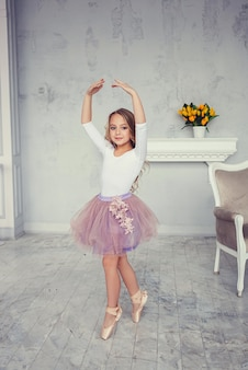 A cute little girl is dancing like a ballerina