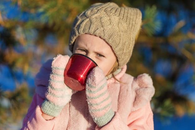 귀여운 소녀는 겨울 숲에서 컵에서 마시고있다. 행복한 어린 시절. kids outdoors. 겨울 재미있는 휴가 개념