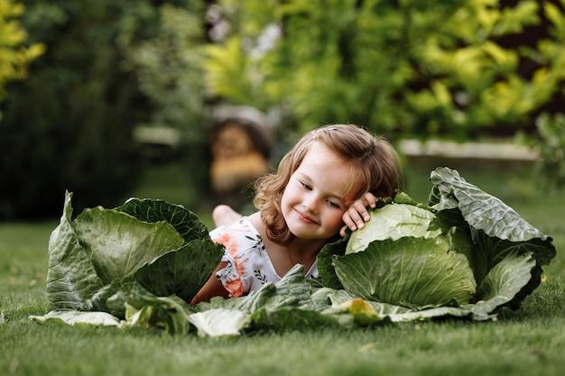 Милая маленькая девочка веселится и лежит на зеленой траве возле капусты.