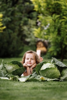 Cute little girl is having fun and lying on green grass near cabbages.