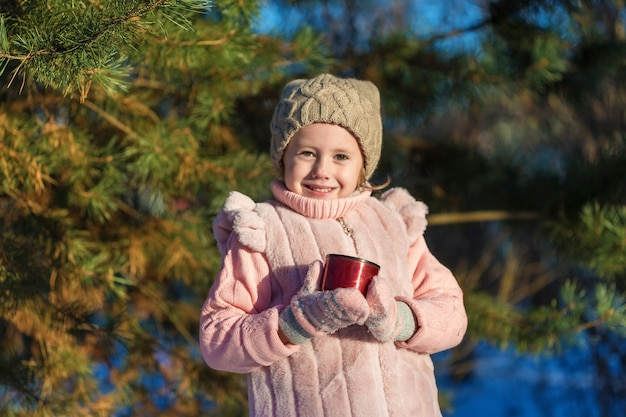 귀여운 소녀는 겨울 숲에서 뜨거운 차 한 잔을 들고있다. 행복한 어린 시절. kids outdoors. 겨울 재미있는 휴가 개념