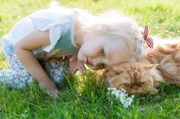 Милая маленькая девочка держит рыжего кота на природе на траве