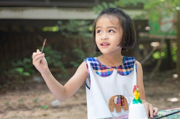 Cute little girl is learning outside the classroom happily with beautiful nature and a bright smile