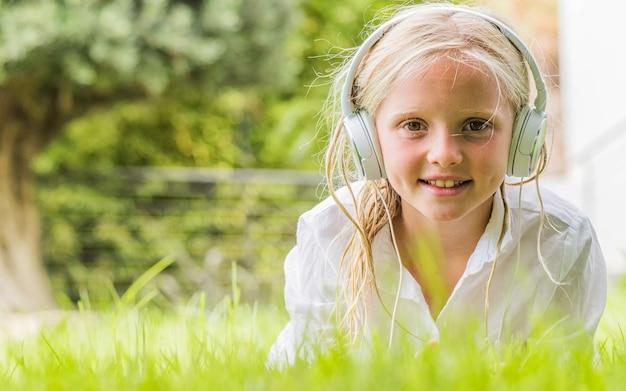 Милая маленькая девочка слушает музыку в парке.