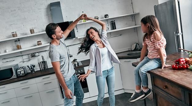Милая маленькая девочка смотрит на своих красивых родителей, танцующих, все улыбаются, проводя время вместе на кухне.