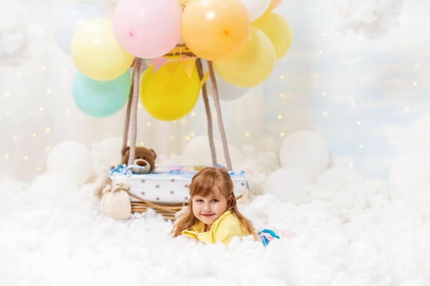 Cute little girl is lying in the clouds next to decorative balloon basket.