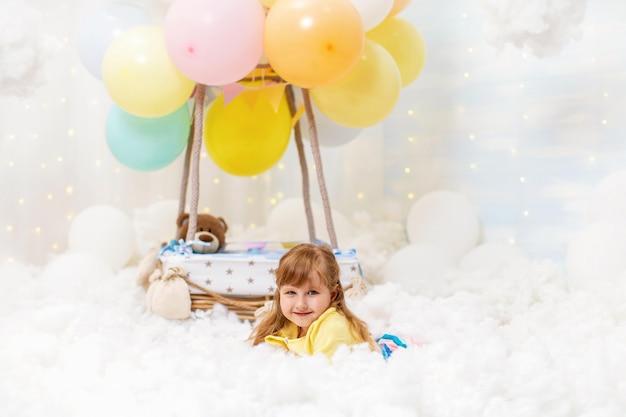かわいい女の子は装飾的なバルーンバスケットの横にある雲の中で横になっています。