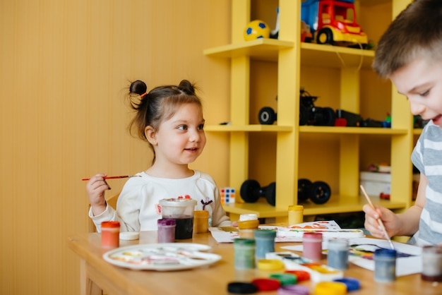 A cute little girl is playing and painting in her room. recreation and entertainment.
