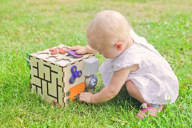 Cute little girl is playing with busiboard outdoors on green grass. educational toy for toddlers. girl opened door to cube of board.