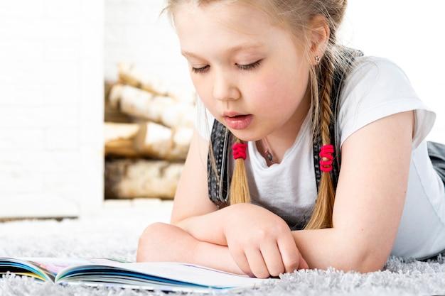 Милая маленькая девочка читает книгу на ковре в квартире