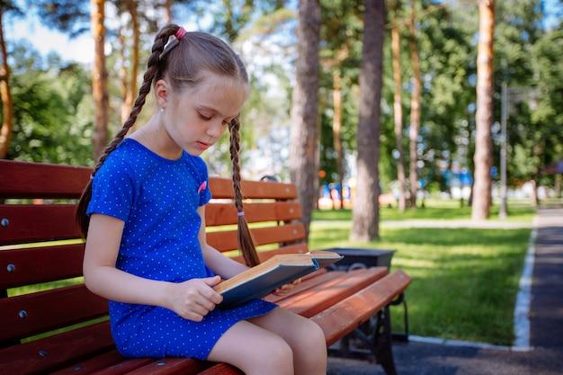 Милая маленькая девочка читает книгу на открытом воздухе