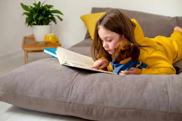 Cute little girl is reading a book lying on the bed with a dwarf dachshund home education