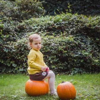 Cute little girl is sitting on a pumpkin