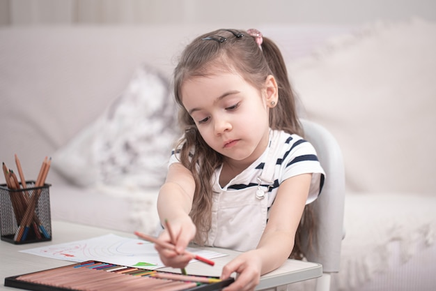 A cute little girl is sitting at the table and doing her homework. homeschooling and education concept.