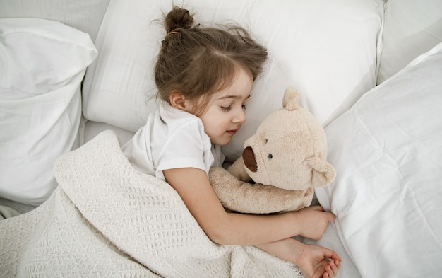 A cute little girl is sleeping in a bed with a teddy bear toy . concept of child development and sleep. the view from the top.