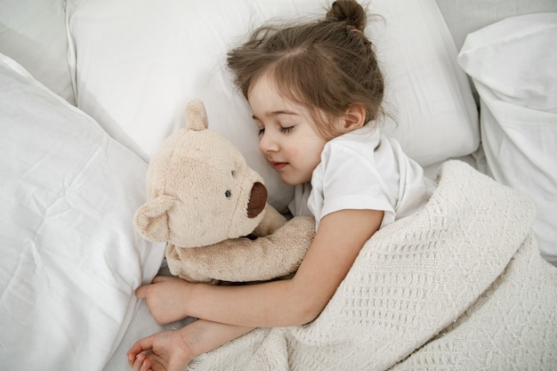 A cute little girl is sleeping in a bed with a teddy bear toy.
