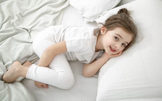 A cute little girl is sleeping in a white bed. concept of child development and sleep.
