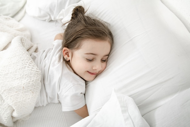 A cute little girl is sleeping in a white bed .