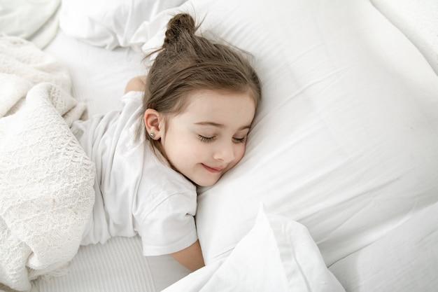 Una bambina carina sta dormendo in un letto bianco.