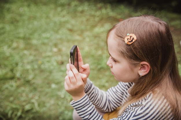 Cute little girl is using the smart phone. grass on background. on girl a hairpin with a pumpkin