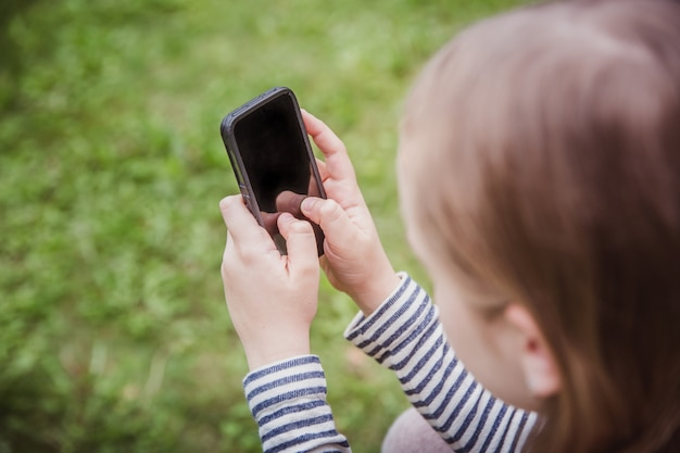 Cute little girl is using the smart phone. grass on background.
