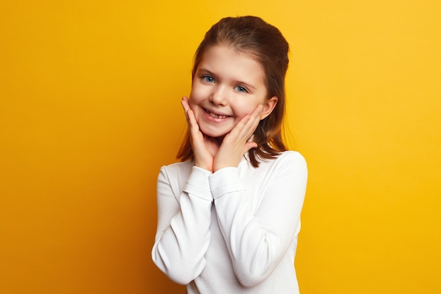 Милая маленькая девочка держит руки на щеках и улыбается у желтой стены