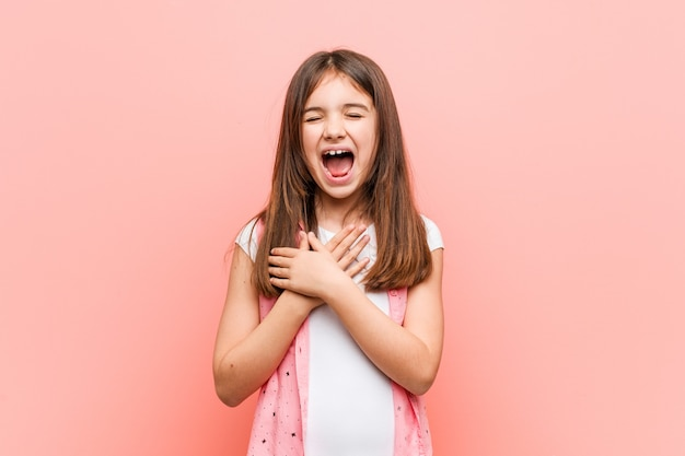 Cute little girl laughing keeping hands on heart,  happiness.