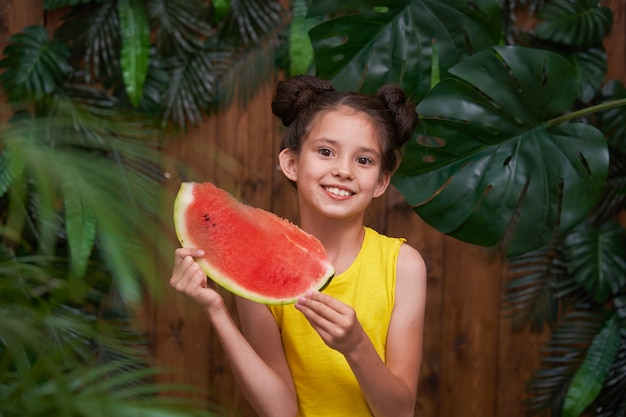 Cute little girl, laughing merrily and holding a piece watermelon in her hands