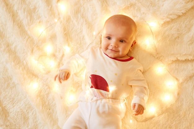 明るいクリスマスの花輪の近くの柔らかいカーペットの上に床に横たわって、魅力的な笑顔で見上げて、白いお祭りの服を着ているかわいい女の子。