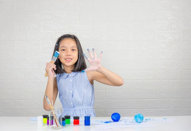Cute little girl learning solar system making model with painting on foam ball
