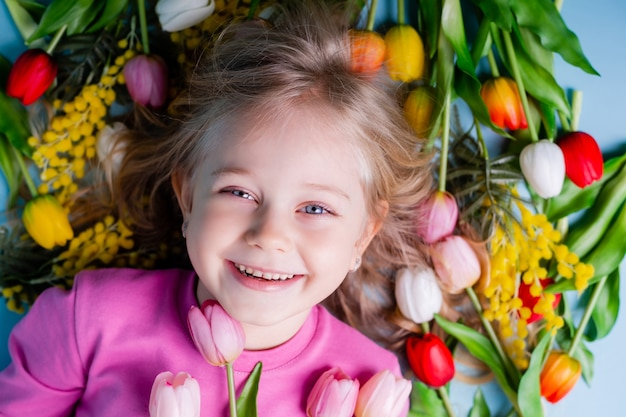 A cute little girl lies among the tulips on a blue background in the studio