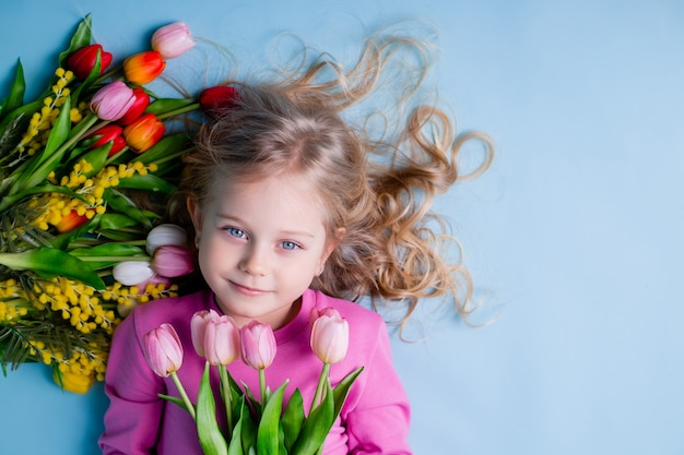 A cute little girl lies among the tulips on a blue background in the studio.