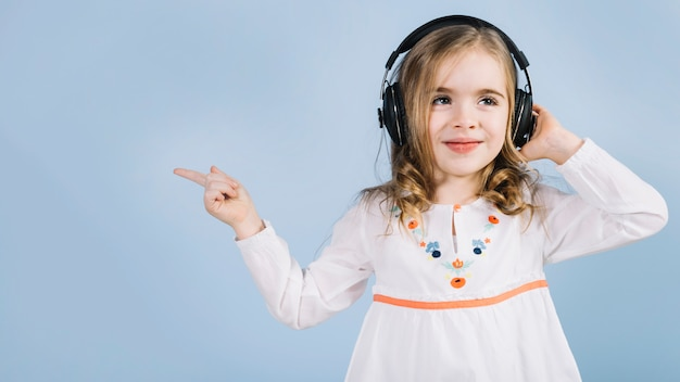 Cute little girl listening music on headphone pointing her finger at something