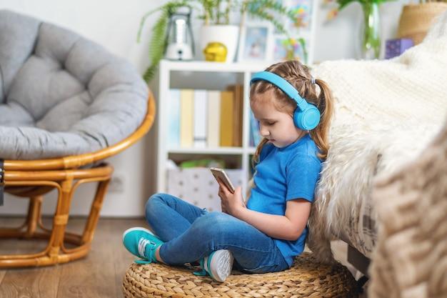 Милая маленькая девочка, слушать музыку в наушниках на смартфоне