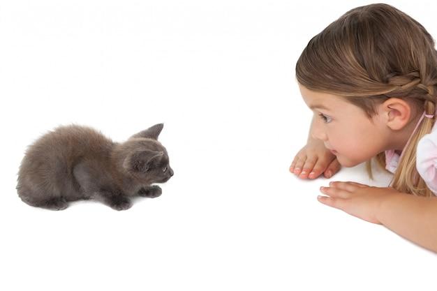 床に横たわる灰色の子猫を見てかわいい女の子