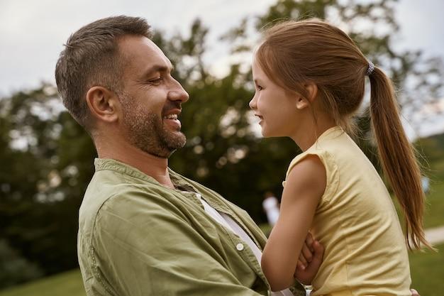 彼女のお父さんを見て、屋外の父と娘の時間を過ごしながら笑っているかわいい女の子