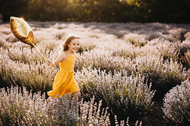 Cute little girl looking at camera smiling while running holding a balloon in a field of flowers.