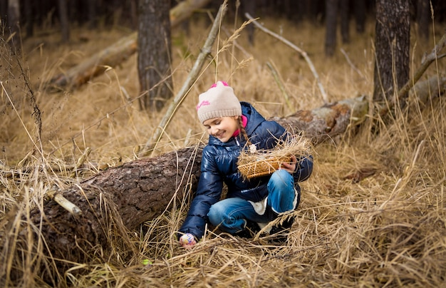 숲에서 로그 아래 부활절 달걀을 찾는 귀여운 소녀
