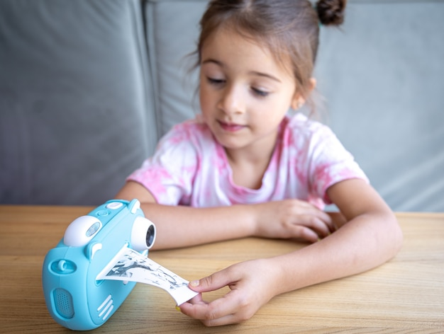 A cute little girl looks at her children's blue toy camera for instant photo printing.