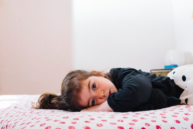Cute little girl lying on bed