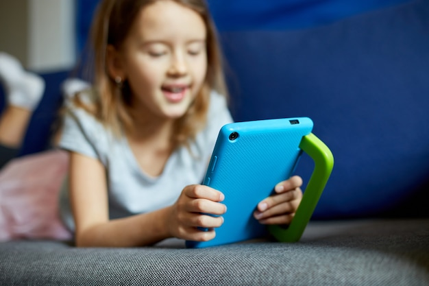 Cute little girl lying on couch, kid addicted to technology, enjoying playing online game on digital tablet computer, using applications, web surfing information at home,
